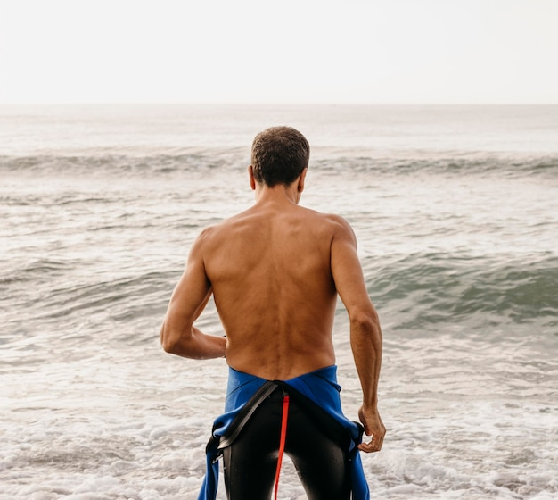 Vista traseira do nadador em forma na praia