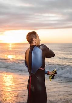 Vista traseira do nadador na praia