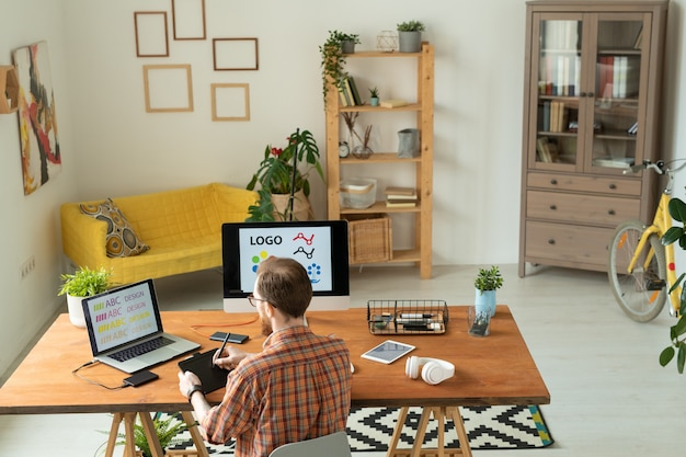Vista traseira do ocupado designer da marca em uma camisa quadriculada sentado na mesa em casa e editando a fonte usando um tablet digitalizador