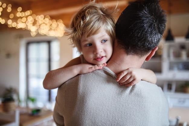 Vista traseira do pai carregando o filho pequeno infeliz doente dentro de casa em casa, confortando-o.