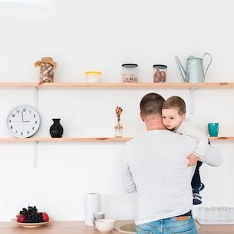 Vista traseira do pai segurando o filho na cozinha