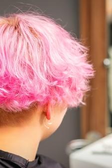 Vista traseira do penteado rosa de uma jovem depois de tingir o cabelo e fazer destaques no salão de beleza
