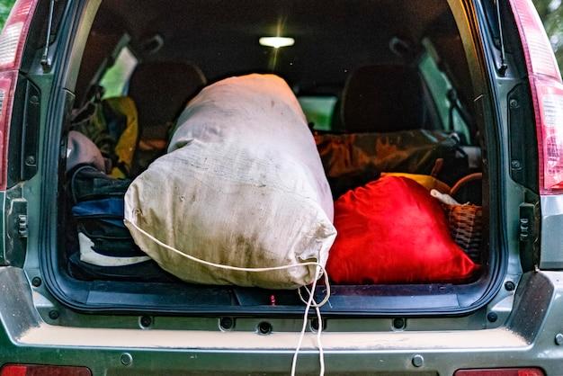 Vista traseira do porta-malas aberto cheio de malas no acampamento da natureza.
