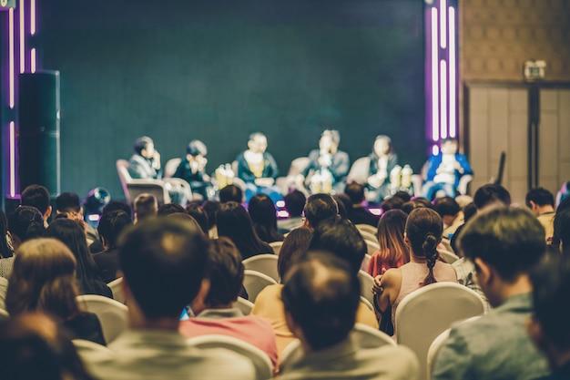 Vista traseira do público asiático, juntando-se e ouvindo o grupo de orador falando no palco