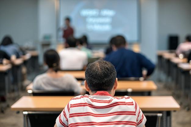 Vista traseira do público ouvindo o orador asiático no palco na sala de reuniões ou conferência