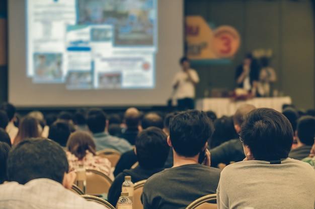 Vista traseira do público ouvindo os palestrantes apresentam o slide no palco da conferência