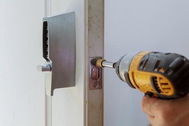 Vista traseira do reparador que instala a chave eletrônica da fechadura da porta.