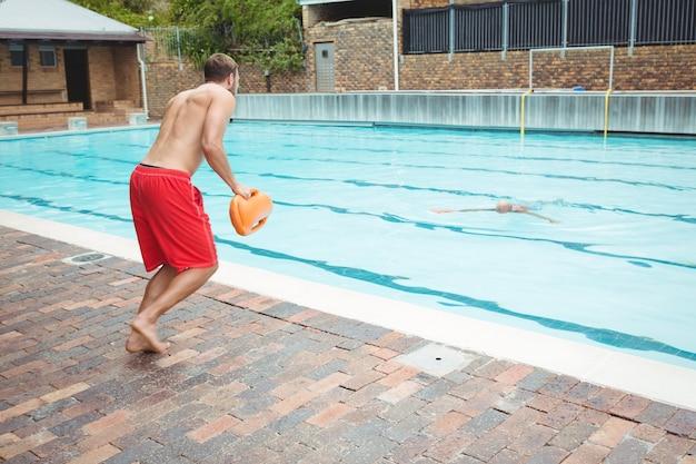 Vista traseira do salva-vidas pulando em uma piscina para resgatar um homem idoso que está se afogando