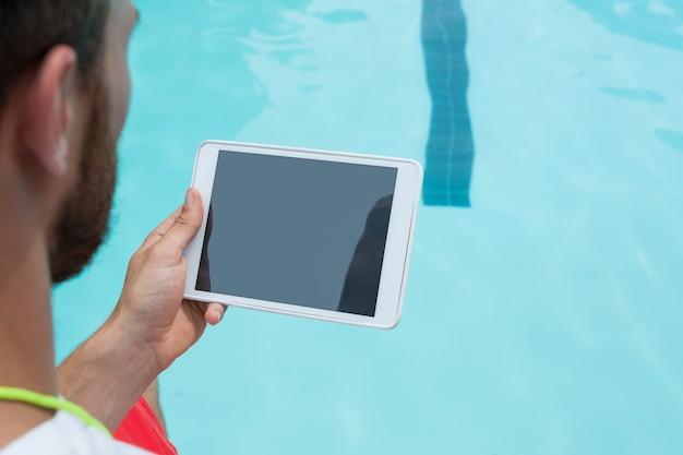 Vista traseira do salva-vidas usando tablet digital ao lado da piscina