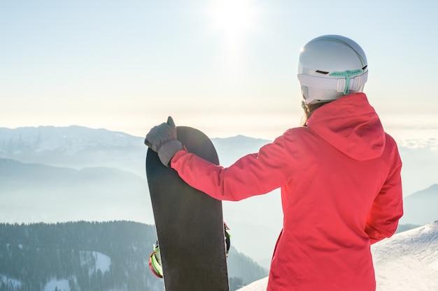 Vista traseira do snowboarder feminino em pé com snowboard e apreciando a paisagem de montanha