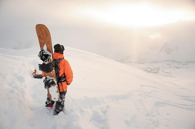 Vista traseira do snowboarder olhando nos picos das montanhas