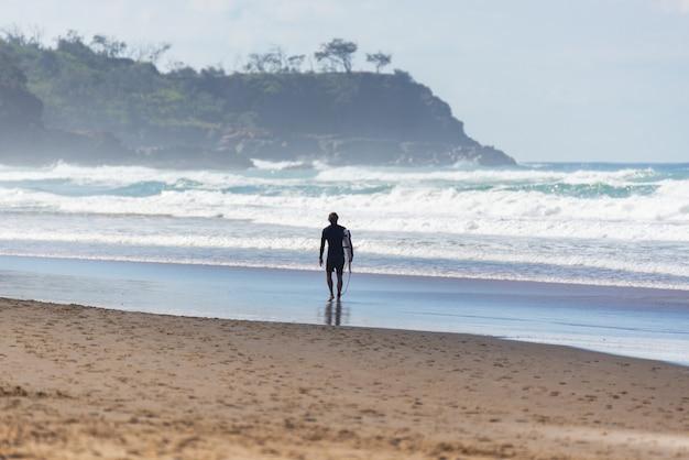 Vista traseira do surfista caminhando em uma praia australiana no verão. water deport concept.listro