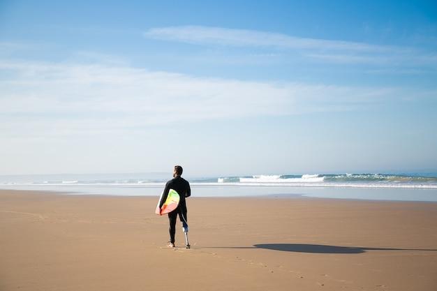 Vista traseira do surfista em pé na praia de areia com prancha