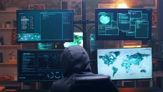 Vista traseira do terrorista cibernético encapuzado usando o supercomputador na sala escura. equipe de hackers.