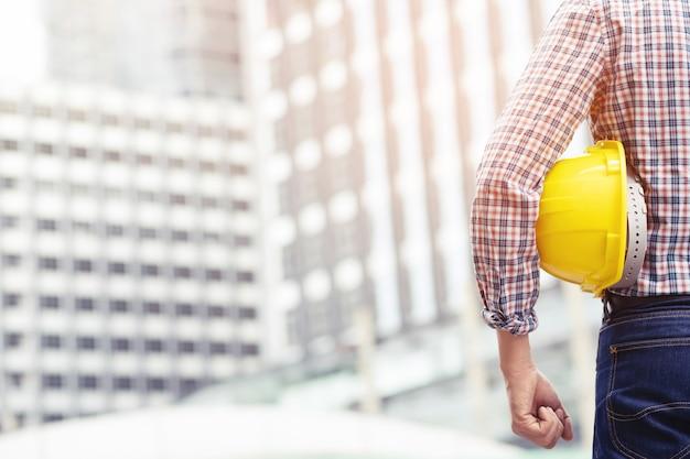 Vista traseira do trabalhador da construção civil homem de engenharia usar capacete de segurança e usar roupas reflexivas para a segurança da operação de trabalho. engenheiro em pé procurando o sucesso do projeto.