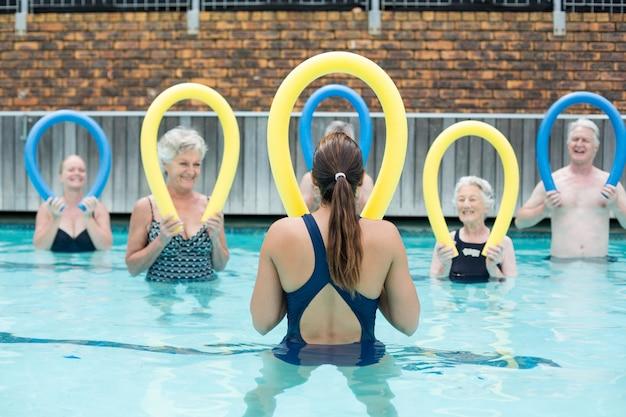 Vista traseira do treinador demonstrando o uso de macarrão de piscina