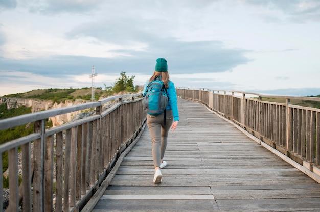 Vista traseira do turista andando pela ponte