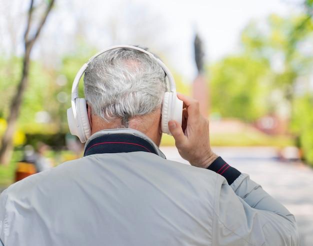 Vista traseira do velho usando fones de ouvido