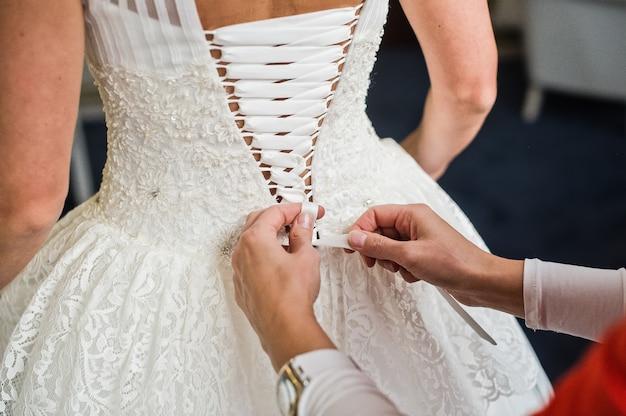 Vista traseira do vestido de noiva, as mãos da mãe amarram o vestido da noiva