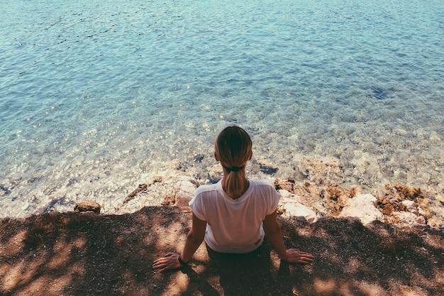 Vista traseira do viajante sentado, segurando os braços na praia, apreciando a paisagem de água do mar e rochas