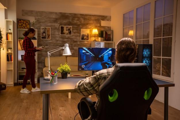 Vista traseira do videogame profissional jogando em um pc poderoso tarde da noite na sala de estar.