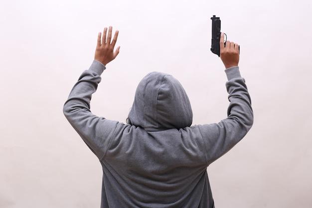 Vista traseira do vilão segurando uma arma com gesto de rendição