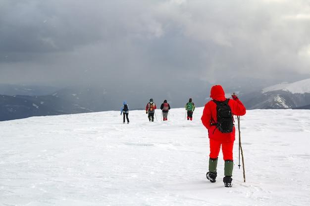 Vista traseira dos caminhantes andando na colina coberta de neve nas montanhas de inverno.