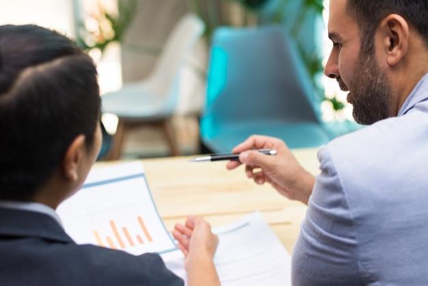 Vista traseira dos especialistas financeiros trabalhando juntos no escritório