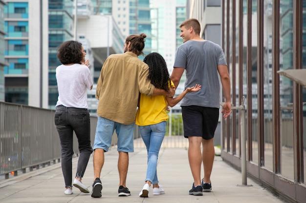 Vista traseira dos jovens andando na rua