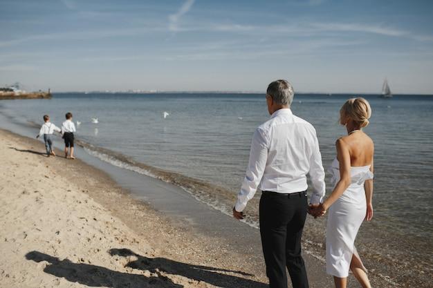 Vista traseira dos pais, que estão de mãos dadas juntos e dois filhos pequenos na frente deles no litoral