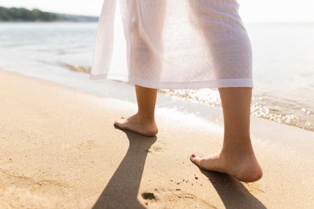 Vista traseira dos pés da mulher nas areias da praia