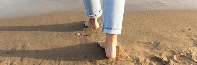 Vista traseira dos pés de mulher nas areias