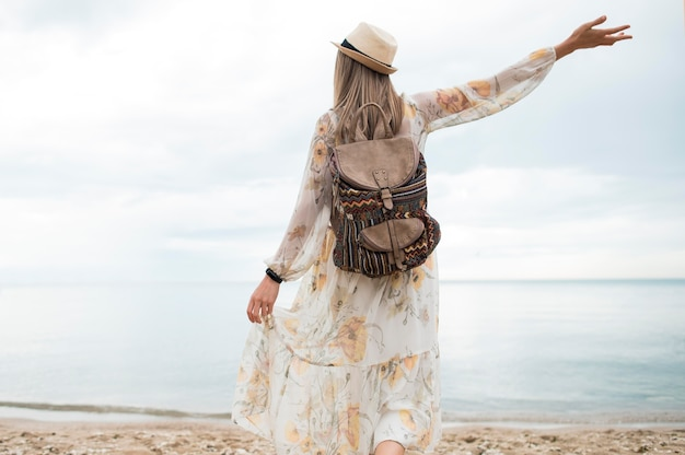 Vista traseira elegante mulher com mochila, aproveitando a viagem