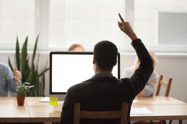 Vista traseira, em, homem africano, levantando mão, celebrando, vitória online, olhar, tela computador