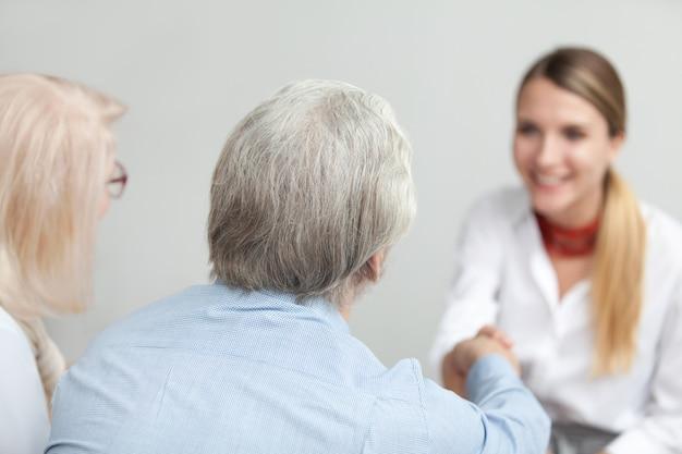 Vista traseira, em, par sênior, handshaking, conselheiro, ou, médico, trabalhador