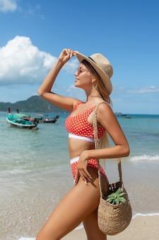 Vista traseira: encantadora loira de cabelos compridos em um maiô vermelho, chapéu de palha e saco de vime posando praia. moda e beleza de praia