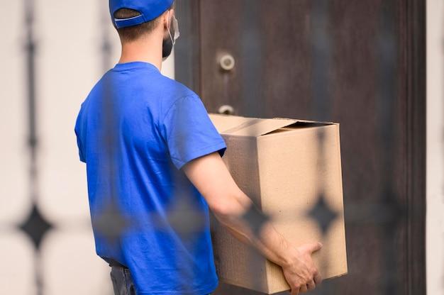 Vista traseira entrega homem carregando remessa