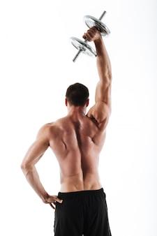 Vista traseira foto de homem forte crossfit, levantando halteres pesados acima de sua cabeça