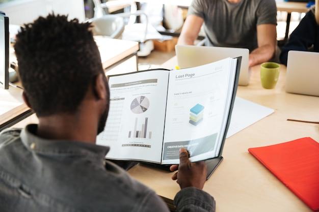 Vista traseira foto do homem africano sentado no escritório de coworking