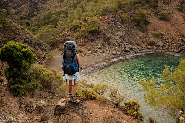 Vista traseira garota com uma mochila de pé em pé sobre a rocha no litoral