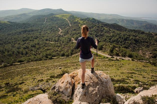 Vista traseira garota de pé sobre a rocha em shorts com bengalas