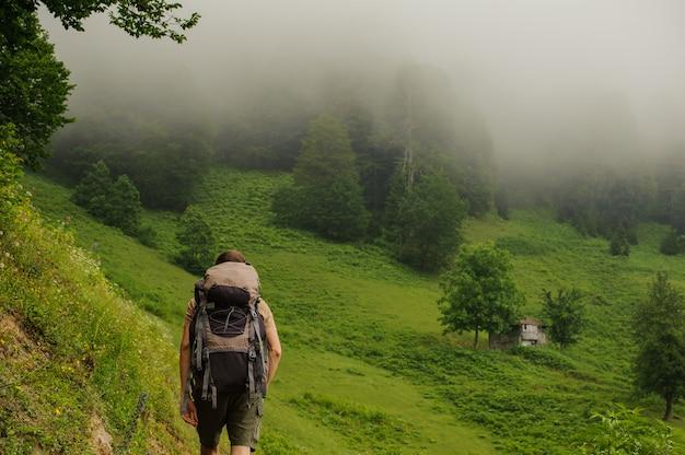 Vista traseira homem andando na colina, olhando para a floresta no nevoeiro