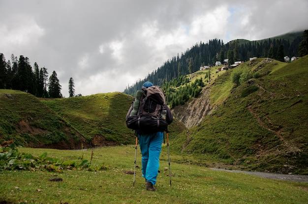 Vista traseira homem caminhando pela colina com caminhadas mochila e paus