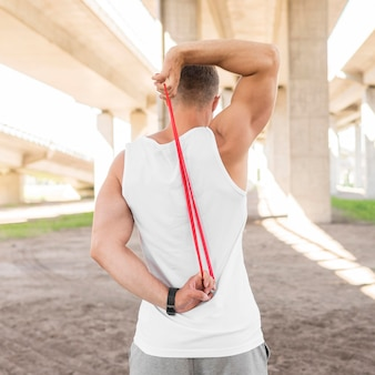 Vista traseira homem malhando com uma faixa vermelha de alongamento