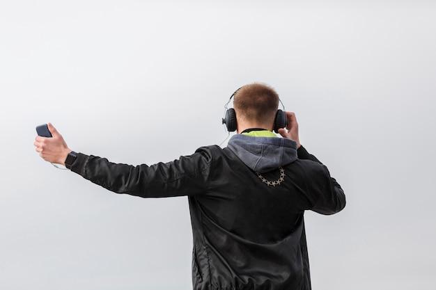 Vista traseira homem ouvindo música fora