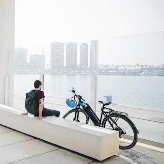 Vista traseira homem sentado ao lado de bicicleta elétrica