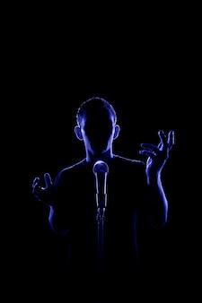 Vista traseira iluminada de um homem sem rosto conversando ou cantando ao microfone