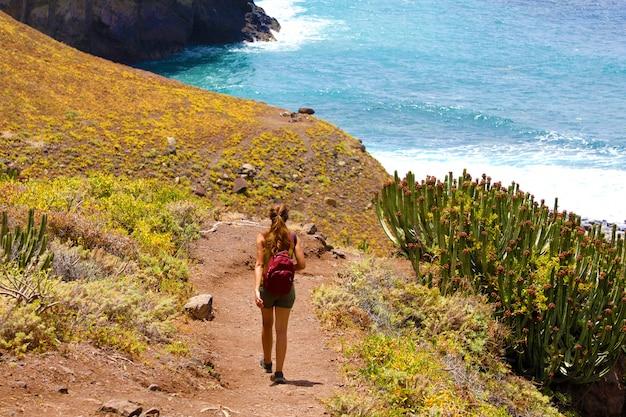 Vista traseira jovem alpinista caminhando em direção ao mar em macizo de anaga em tenerife