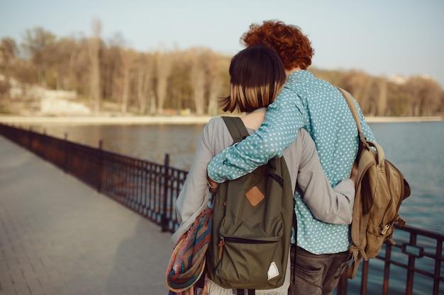 Vista traseira jovem casal andando despreocupado no parque perto do lago