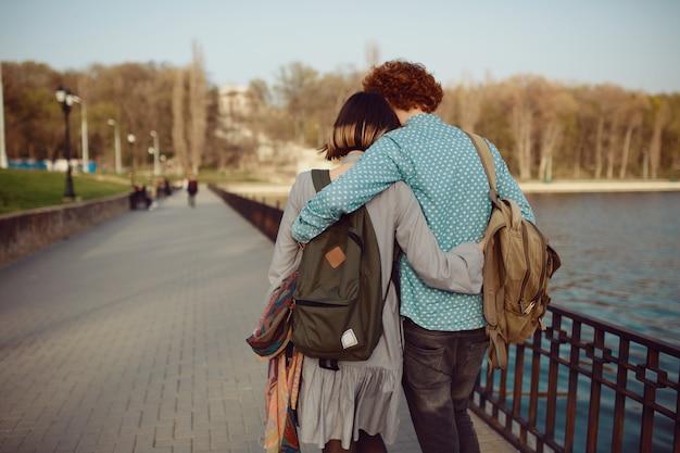 Vista traseira jovem casal com mochilas andando despreocupado no parque perto do lago